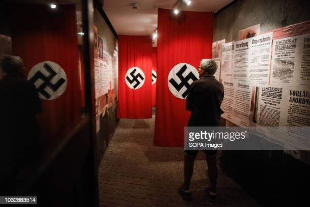 A man seen observing a Nazi flag during the exhibition Exhibition at Oskar Schindler's Enamel Factory museum it is primarily a story about Krakow and...