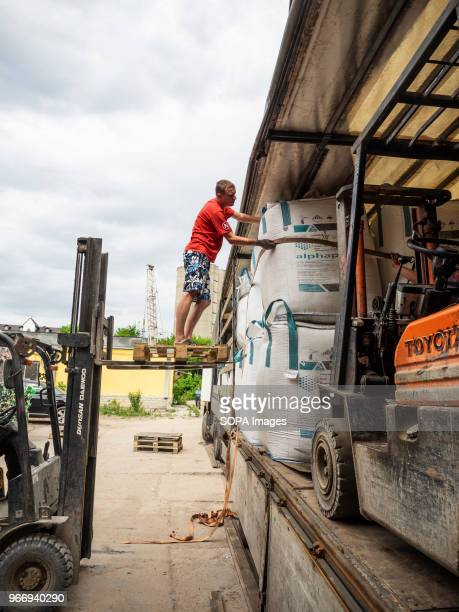 A man seen on top of a forklift while loading big bags with crushed plastic bottles into the truck to be sent for further processing In Ukraine...