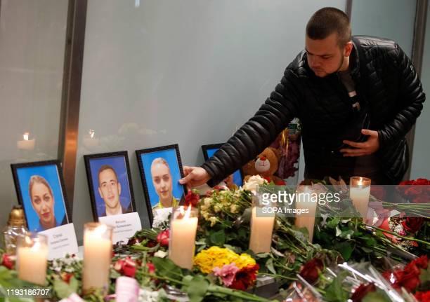 A man seen placing a portrait of a victim of flight PS 752 at the memorial corner of Boryspil International Airport Ukrainian international airlines...