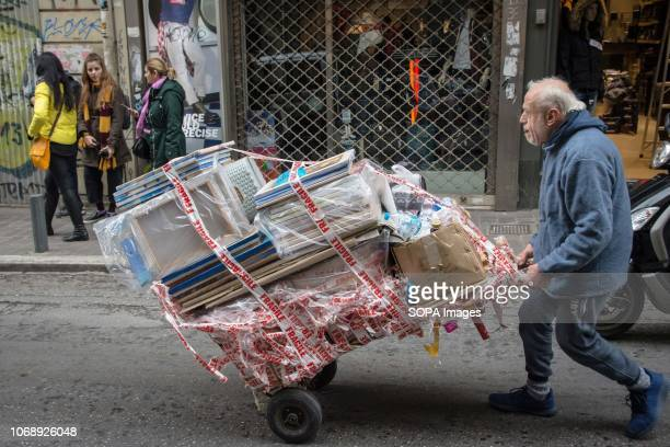 A man seen pushing a stroller with packages in the center of Athens Greece