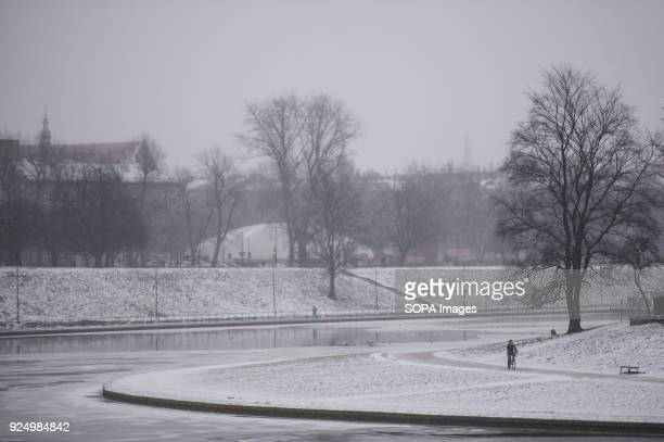 A man seen riding a bicycle next to Vistula river in Krakow