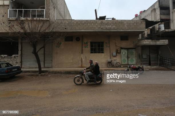 A man seen riding with his daughter on a motorcycle during the winter in the street of Mesraba Despite the ongoing conflict in Syria life in...