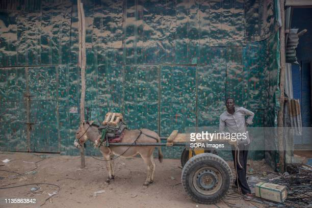 Man seen standing next to a donkey with a cart in the refugee camp. Dadaab is one of the largest refugee camps in the world. More than 200,000...
