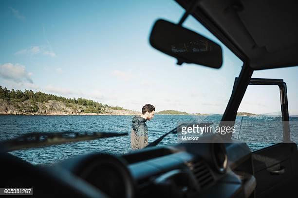 Man seen through car windshield at lakeshore
