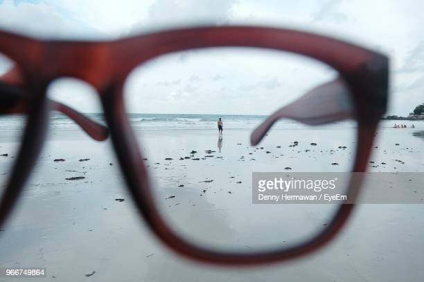 man seen through eyeglasses at beach - looking through an object stock pictures, royalty-free photos & images