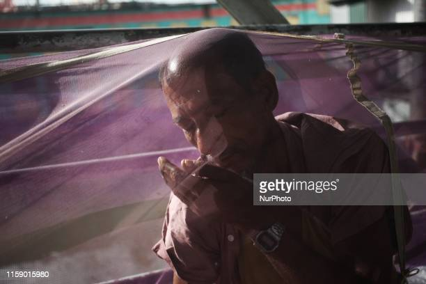 A man seen wake up from sleep under a mosquito net in Dhaka Bangladesh on 2 August 2019