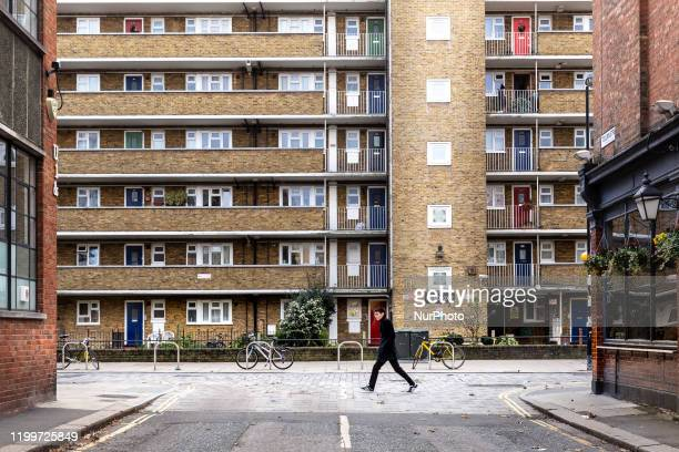 Man seen walking in front of a block of flats in Southbank district of London England on December 1, 2019.