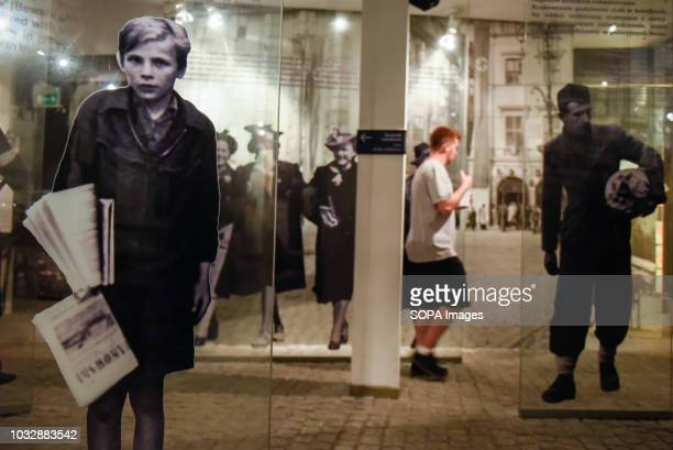 A man seen walking through glass displays during the exhibition Exhibition at Oskar Schindler's Enamel Factory museum it is primarily a story about...