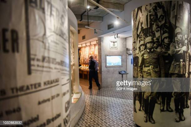A man seen walking through one of the exhibition rooms during the exhibition Exhibition at Oskar Schindler's Enamel Factory museum it is primarily a...