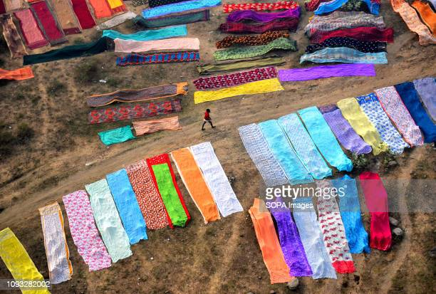 A man seen walking through the colourful cloth spread on the soil next to the river bank of Barakar in Jharkhand area The Dhobi Ghat of Kumardubi in...