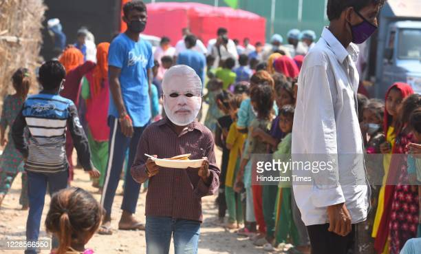 A man seen wearing a mask of Prime Minister Narendra modi during a community feeding session for Hindu refugees from Pakistan on the occasion of...