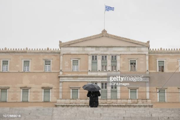 A man seen with an umbrella at the center of Athens front of the Greek Parliament on a rainy day