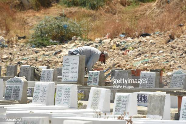 """Man seen working on a grave at the El jalez cemetery. The health ministry spokeswoman described the virus's affect in Tunisia as """"catastrophic"""". The..."""