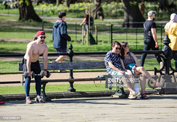 Man seen working out at Kensington Gardens as Londoner's enjoy the sunshine on the hottest day of 2021 so far.