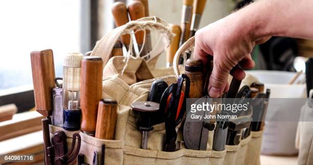 Man selecting a hand tool from a bag on workbench
