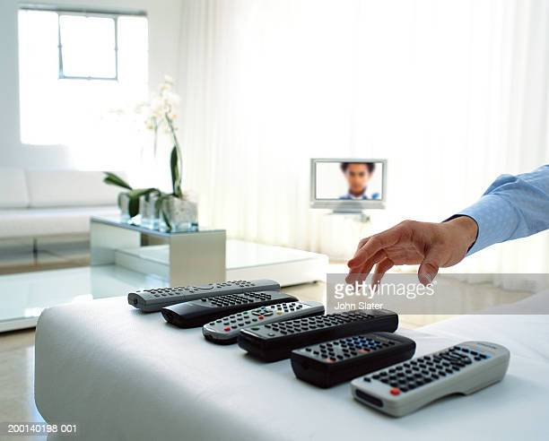 Man selecting remote control handset