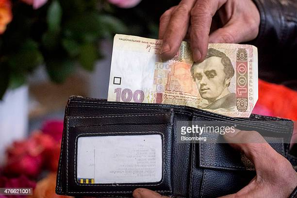 A man selects a 100 hryvnia banknote from his wallet in this arranged photograph in Kiev Ukraine on Tuesday March 4 2014 Moscow's move to seize...