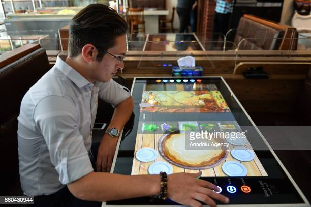 A man selects his food served by robot waiter which moves on rail system placed between tables at the first robotic restaurant 'RoboChef' in Tehran...