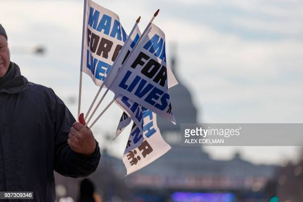 A man sell flags as people arrive early for the March For Our Lives rally against gun violence in Washington DC on March 24 2018 / AFP PHOTO / Alex...