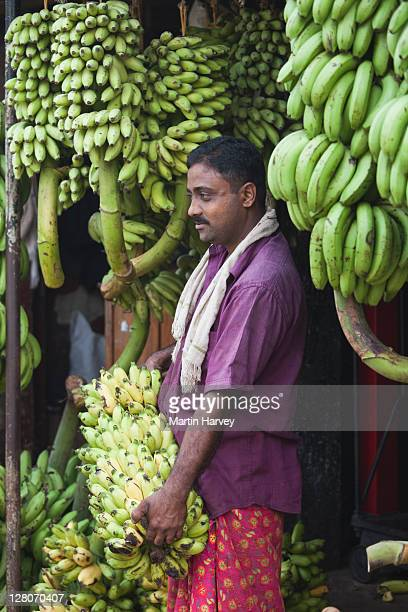 man (57 years old) selling bunches of green bananas at the fruit and vegetable market in ernakulam, kochi, kerala, india - 55 59 years stock pictures, royalty-free photos & images
