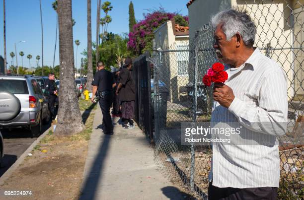 A man selling carnations watches as police officers check the identities of possible street gang members against a fence May 21 2017 after the group...