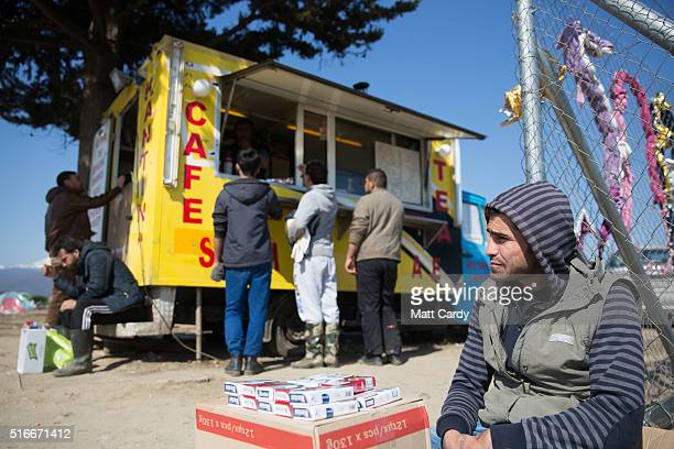 A man selling cigarettes sits beside a catering van at the Idomeni refugee camp on the Greek Macedonia border on March 20 2016 in Idomeni Greece...