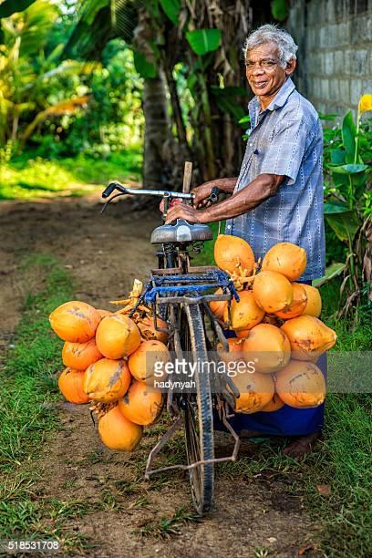 Mann, Verkauf von Kokosnüsse aus seinem Fahrrad nahe Mirissa, Sri Lanka