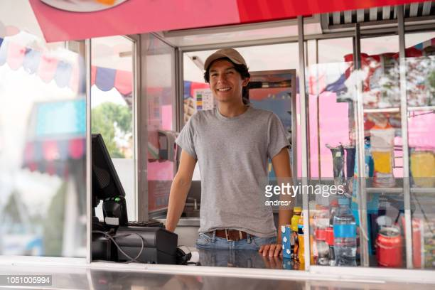 man selling food in a truck at an amusement park - kiosk stock pictures, royalty-free photos & images