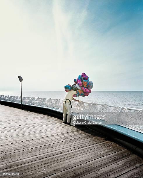 Man selling helium balloons at seaside