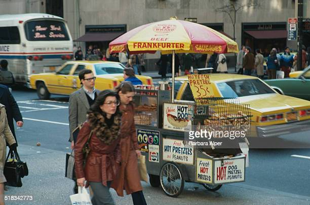 A man selling hot dogs and pretzels from a cart New York City USA April 1980