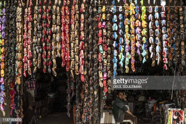 Man selling infant shoes waits for customers in the northern Syrian city of Raqa, the former Syrian capital of the Islamic State group, on April 14,...