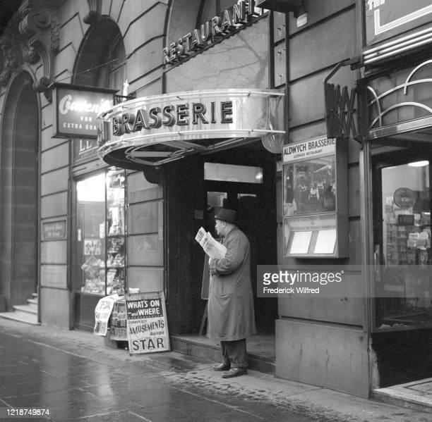 Man selling newspaper outside a brasserie in Aldwych, London, UK, circa 1960.
