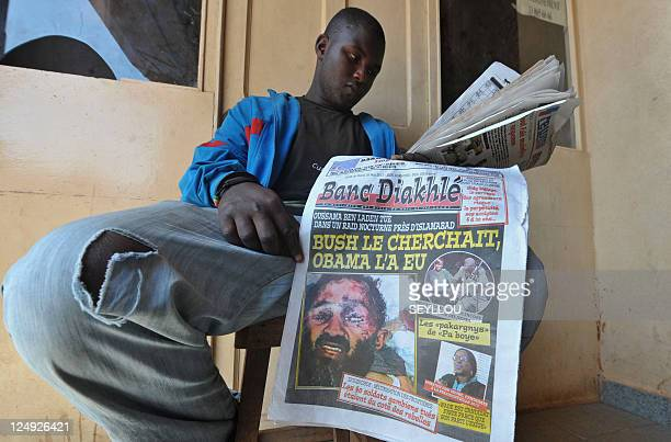 A man selling newspapers in Dakar displays the front page of a paper on his lap which features a fake photo of AlQaeda leader Osama Bin Laden's...