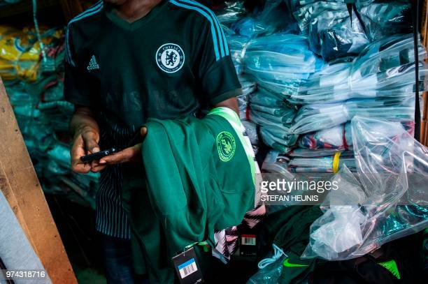 Man selling Nigerian World Cup jerseys is pictured in Balogun Market in Lagos on June 14, 2018. - The Nigeria Super Eagles jersey for the 2018 World...