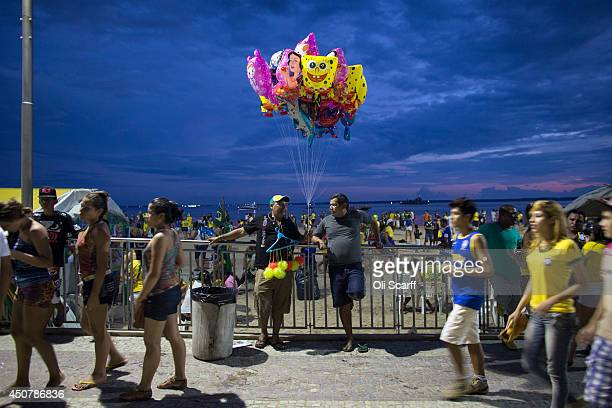 A man selling novelty helium balloons waits on the beachfront outside the Fan Fest area in Porta Negro shortly after the end of Brazil's game against...