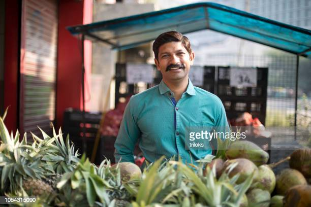 man selling pineapple and coconut - india market stock photos and pictures