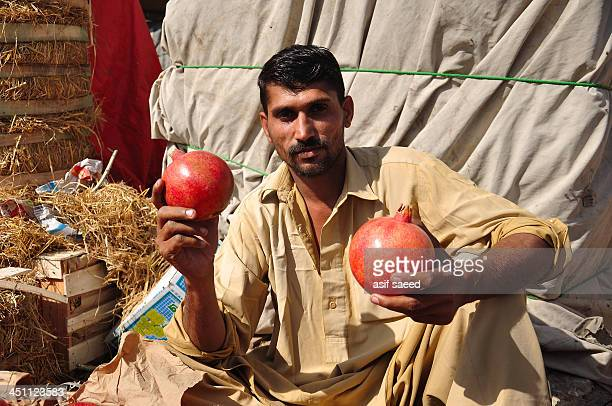 Man selling pomegranates At Islamabad Sabzi Mandi. Islamabad Pakistan