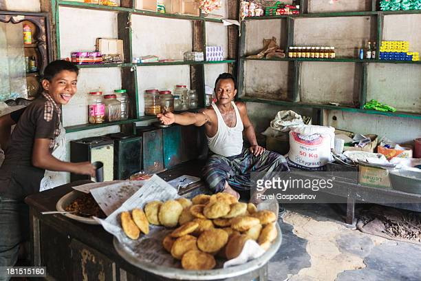 CONTENT] Man selling samosas at a local store in rural Bangladesh around Srimangal Indian SubContinent Asia