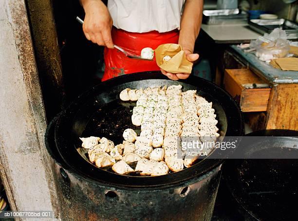 Man selling Shanghai dumplings at street shop, mid section