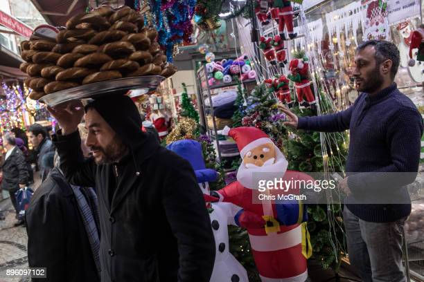 A man selling Simit stands in front of a store displaying Christmas decorations on December 20 2017 in Istanbul Turkey Some luxury brands shopping...
