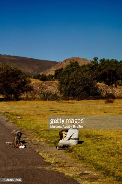 man selling souvenirs at roadside while sitting on grass against sky - mariana abad fotografías e imágenes de stock