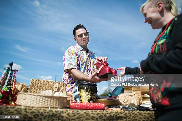 Man selling sparkly shoes at yard sale