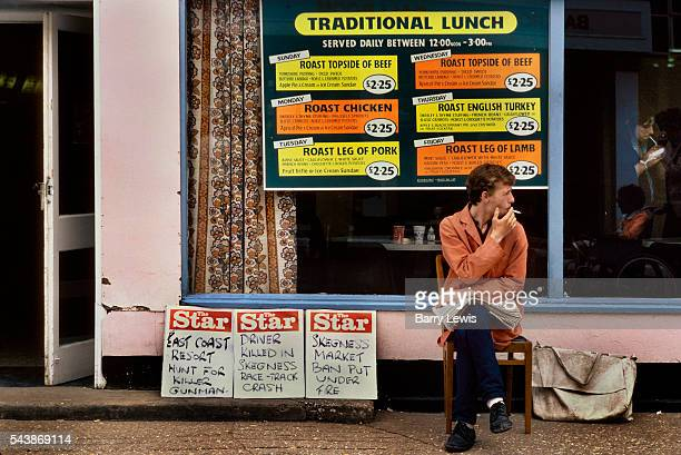 Man selling the local paper in front of the traditional dining room in Butlins Holiday camp Skegness Butlins Skegness is a holiday camp located in...
