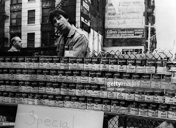 Man selling tins of Campbell's soup with altered names such as 'Cat Chowder', 'Cream of Child' and 'Pig in Shit' on a New York street.
