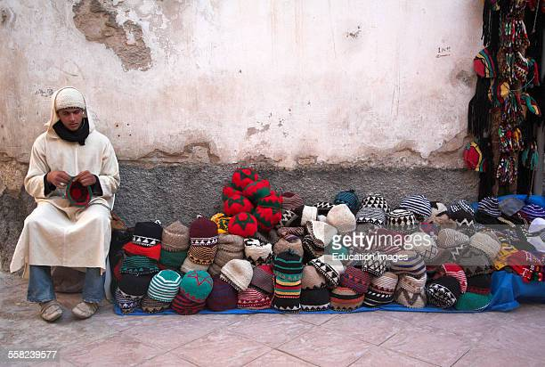 Man selling wool hats from a street stall Essaouira Morocco north Africa