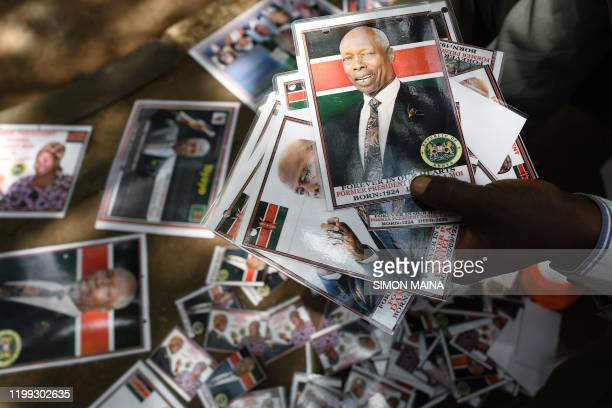 A man sells badges bearing the photo of late former Kenya's President Daniel Arap Moi outside Parliament Buildings where it would LieinState for...
