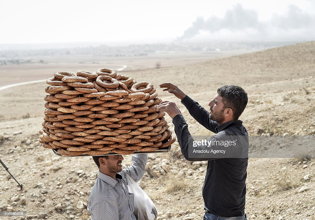 A man sells bagels as Turkish residents watch the clashes between the Islamic State of Iraq and the Levant (ISIL) and Kurdish armed groups in the Syrian border town of Kobani (Ayn al-Arab) from Suruc district of Sanliurfa, Turkey on October 10, 2014.