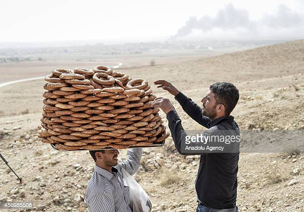A man sells bagels as Turkish residents watch the clashes between the Islamic State of Iraq and the Levant and Kurdish armed groups in the Syrian...