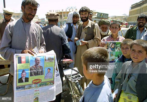 A man sells calendars featuring portraits of Interim Leader Hamid Karzai former King Zahir Shah and assassinated Northern Alliance leader Ahmed Shah...