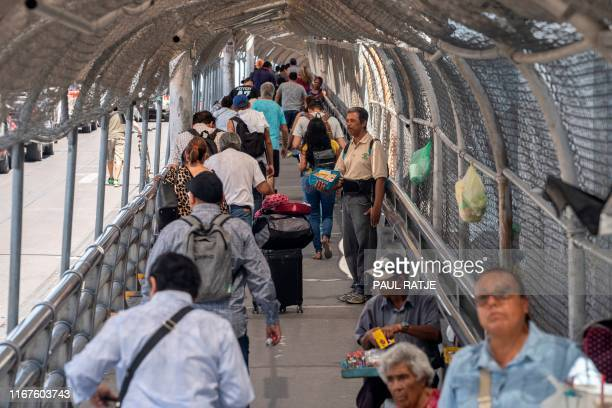 TOPSHOT A man sells candy as pedestrian commuters make their way across the Paso del Norte Bridge at the MexicoUS border in Ciudad Juarez Mexico on...